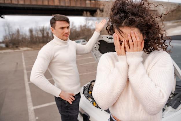 Europäische ehepaare streiten über kaputtes auto. wütender erwachsener mann ist unzufrieden. frustriertes lockiges gesicht der jungen frau. öffnen sie die motorhaube. leute im freien