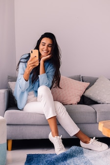 Europäische fit brünette modebloggerin sitzt auf dem boden im wohnzimmer nahe sofa