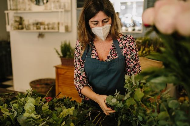 Europäische floristin mit medizinischer gesichtsmaske, die blumenarrangements im blumendesignstudio herstellt