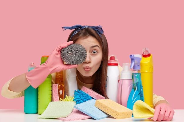 Europäische frau bedeckt auge mit schwamm, trägt stirnband, schutzhandschuhe, kümmert sich um hygiene und hygiene, verwendet chemische reinigungsmittel zum spülen von geschirr