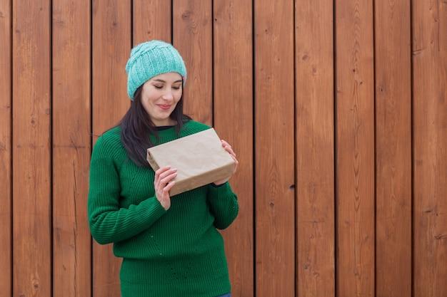 Europäische frau im grünen pullover mit geschenk.