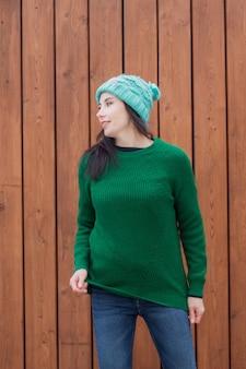 Europäische frau im grünen pullover und im grünen hut auf holzwand.