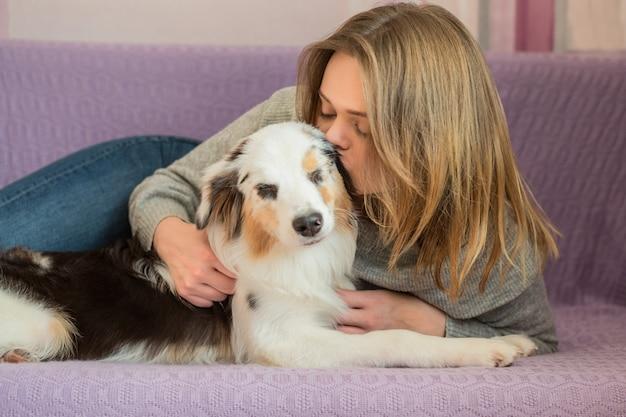 Europäische frau in der jacke, die australischen schäferhund küsst, der auf sofa liegt