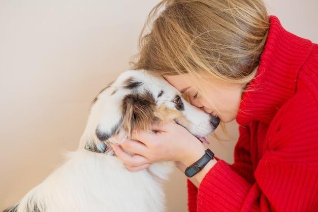Europäische frau in roter jacke mit australischem schäferhund