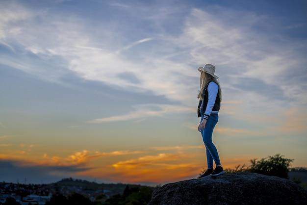 Europäische frau mit cowboyhut, die auf einem felsen steht und den sonnenuntergang beobachtet