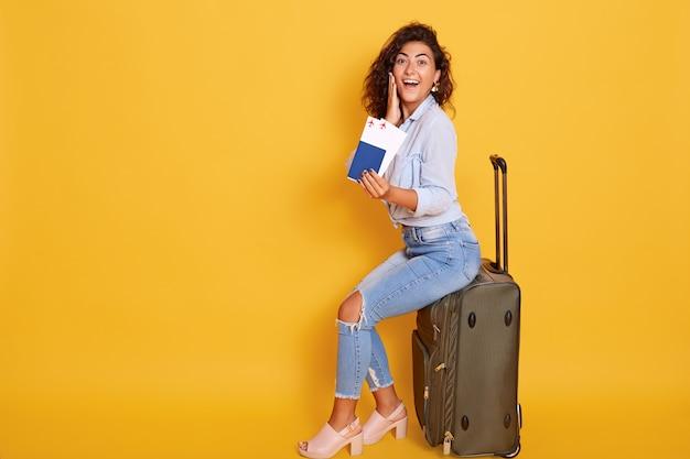 Europäische frau mit pass und ticket sitzt auf koffer und sieht glücklich und aufgeregt aus