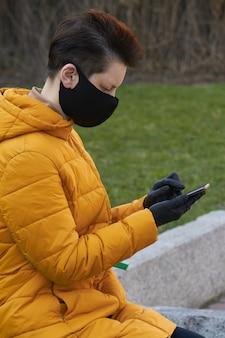 Europäische frau mittleren alters in schützender schwarzer maske und handschuhen, die ein smartphone außerhalb während der coronavirus-covid-19-epidemie halten