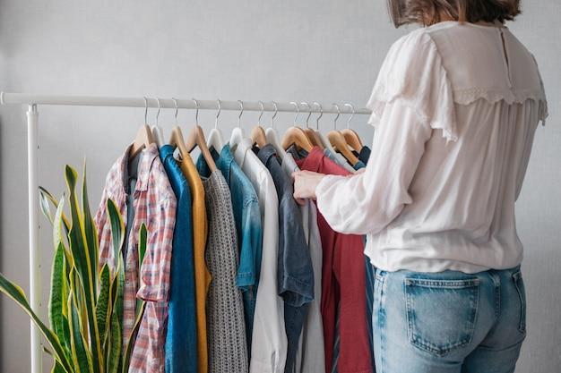 Europäische frau zu hause im kleiderschrank wählt kleidung für eine party oder geburtstagsfeier aus und sortiert kleidung