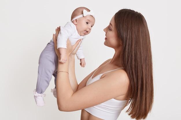 Europäische fröhliche schöne junge frau, die baby in ihren händen hält und sie mit liebe lokalisiert über weißem hintergrund betrachtet, kleines mädchen mit mama, die haarband mit bogen trägt.