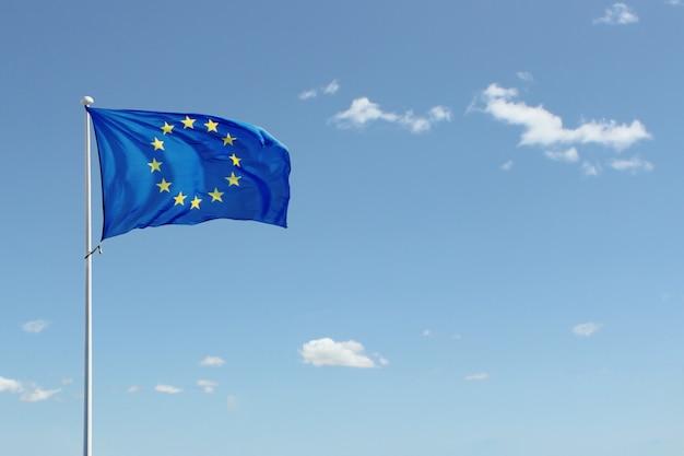 Europäische gemeinschaft fahnenschwenkend gegen hintergrund des blauen himmels