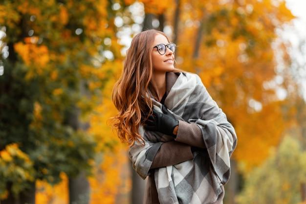 Europäische hipsterfrau in einem modischen gestrickten schal in stilvollen gläsern in einem trendigen mantel, der in einem park außerhalb der stadt aufwirft. mädchen mit einem niedlichen lächeln geht in den wald. elegante herbstkleidung für frauen