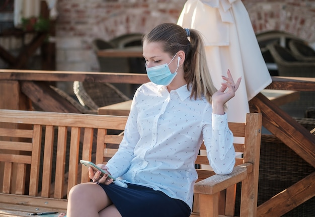 Europäische junge frau, die eine medizinische schutzmaske trägt, sitzt auf einer bank und kommuniziert mit einem smartphone. konzept der physischen distanz und der sozialen distanzierung.