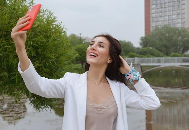 Europäische junge frau im weißen anzug nimmt selfie auf und smartphone im park im sommer