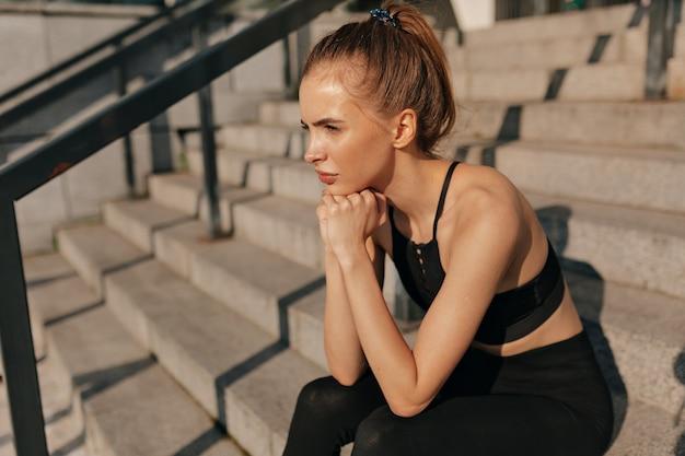 Europäische junge frau in der schwarzen sportuniform, die auf betontreppe sitzt.