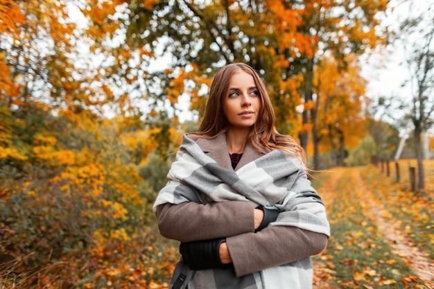 Europäische junge frau in einem warmen strickschal in einem eleganten mantel genießt einen spaziergang durch den herbstwald außerhalb der stadt. das stilvolle niedliche mädchenmodemodell in der modischen oberbekleidung genießt eine pause im park