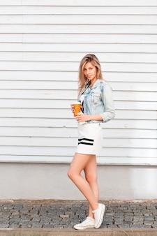 Europäische junge frau in einem weißen kleid in einer jeansjacke in stilvollen turnschuhen posiert in der nähe einer vintage holzwand und hält eine orange tasse kaffee. modisches mädchen, das im urlaub ruht.