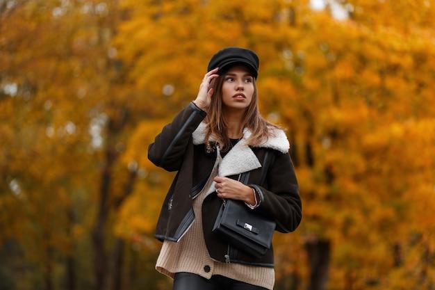 Europäische junge frau in stilvollen kleidern in einem weinlesehut mit einer schwarzen ledertasche, die in einem park aufwirft. attraktives modisches mädchenmodemodell im wald auf einem hintergrund von goldblättern. herbststil.