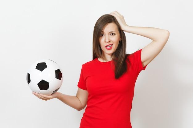 Europäische junge traurige verärgerte frau, fußballfan oder spieler in roter uniform hält fußball, hand auf dem kopf, sorgen über das verlierende team isoliert auf weißem hintergrund. sport, fußball spielen, lifestyle-konzept.