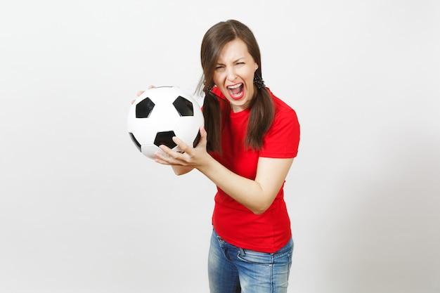 Europäische junge verrückte wütende schreiende frau, zwei lustige pferdeschwänze, fußballfan oder spieler in roter uniform, die fußball isoliert auf weißem hintergrund hält. sport fußball spielen, gesundes lifestyle-konzept.
