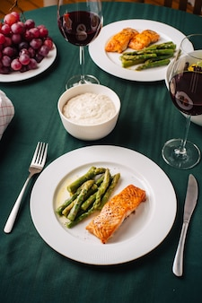 Europäische küche. lachssteak mit spargel, gemüsesalat, sauce, trauben und brot mit gläsern rotwein. abendessen für zwei in der küche