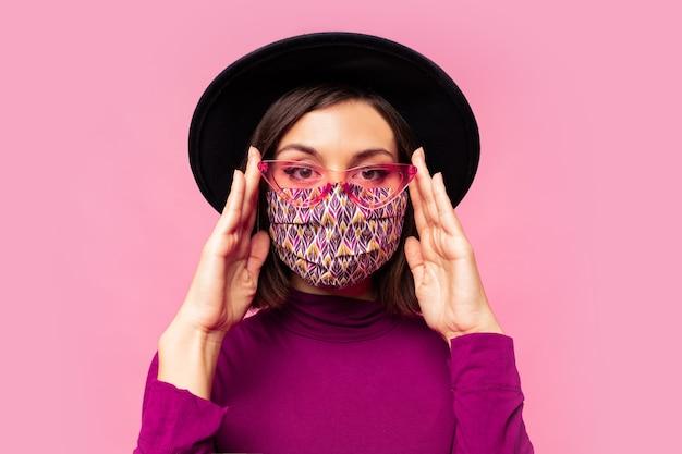 Europäische modell gekleidete schützende stilvolle gesichtsmaske. trägt schwarzen hut und sonnenbrille.