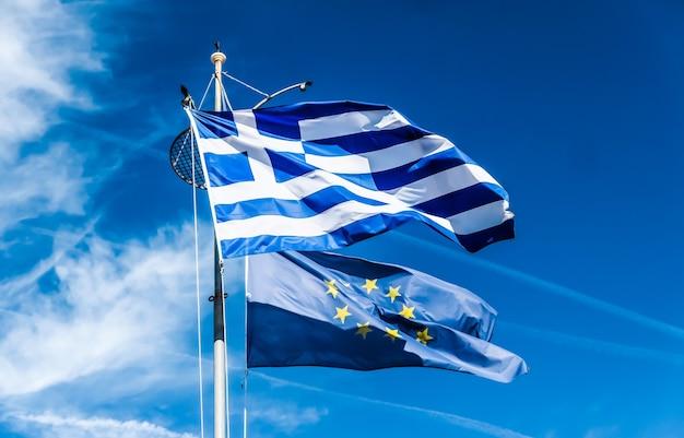 Europäische politische nachrichten grexit und nationenkonzeptflaggen von griechenland und der europäischen union am blauen himmel