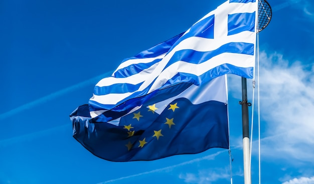 Europäische politische nachrichten grexit und nationenkonzeptflaggen von griechenland und der europäischen union auf blauem himmel hintergrundpolitik europas