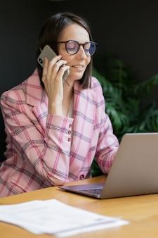 Europäische selbstbewusste geschäftsfrau in einer rosa jacke und mit einem laptop in ihrem büro arbeiten