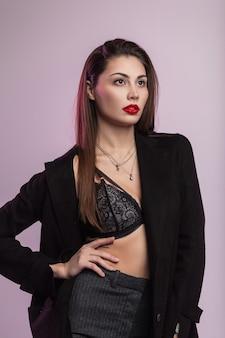 Europäische sinnliche junge frau mit roten lippen in einer langen jacke in vintage-gestreiften hosen in einer sexy modischen spitzenunterwäsche, die im studio nahe der wand posiert. schönes mädchen des mode-modells drinnen.