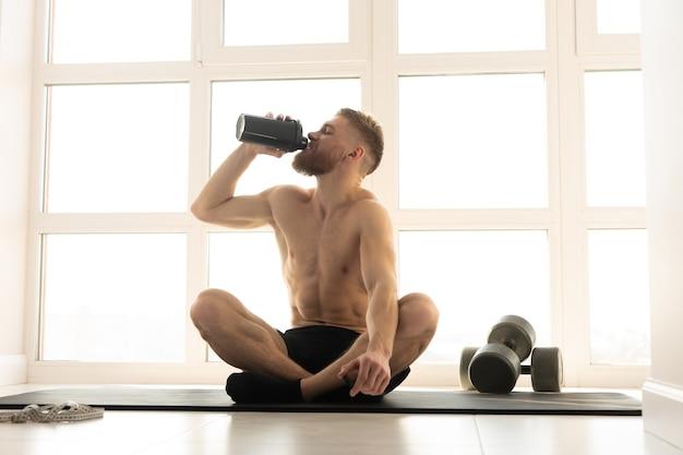 Europäische sportler trinkwasser aus flasche auf fitnessmatte. junger bärtiger mann mit nacktem oberkörper. konzept der sportlichen aktivität zu hause. innenraum der modernen geräumigen wohnung. sonniger tag