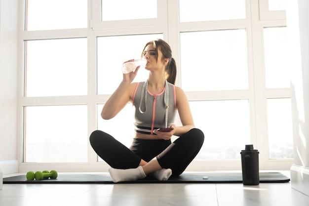 Europäische sportlerin, die zu hause auf fitnessmatte sitzt und wasser aus der flasche trinkt. junge schöne frau trägt sportkleidung. konzept der körperfigurenpflege. innenraum der modernen geräumigen wohnung. sonniger tag