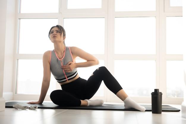 Europäische sportlerin mit herzschmerzen nach dem training auf fitnessmatte sitzend. junge schöne frau trägt sportkleidung. konzept der sportlichen aktivität zu hause. innenraum der modernen geräumigen wohnung. sonniger tag