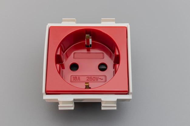 Europäische steckdose in rot auf grauem hintergrund. elektriker zu hause. nahansicht. voller fokus. platz kopieren.