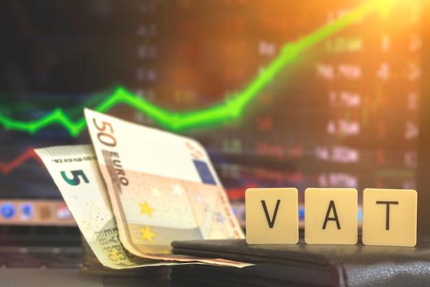 Europäische steuern, mehrwertsteuerkonzept, mehrwertsteuerwort und euro-geldbanknoten auf aktiendiagrammhintergrund. geschäfts- und wirtschaftsfoto
