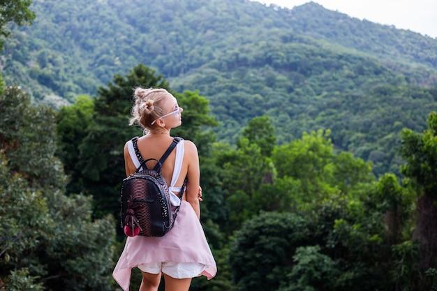 Europäische stilvolle bloggerin der stilvollen frau steht auf der spitze des berges mit erstaunlicher tropischer ansicht der koh samui insel thailand mode-außenporträt der frau