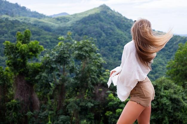 Europäische stilvolle frau touristin steht auf der spitze des berges mit erstaunlicher tropischer ansicht der koh samui insel thailand mode-außenporträt der frau