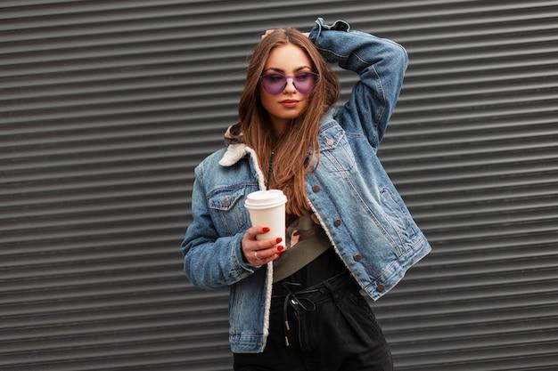 Europäische süße junge hipster frau in modischer jeansblauer jacke in trendigen violetten gläsern mit einer tasse heißen kaffees steht in der nähe einer grauen wand in der stadt. städtisches schönes mädchen, das auf der straße aufwirft.