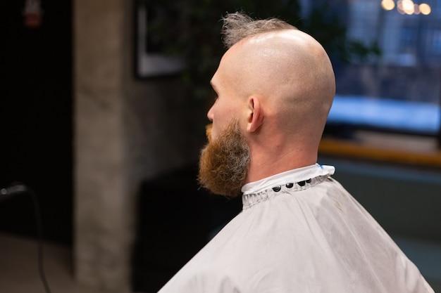 Europäischer brutaler mann mit einem bartschnitt in einem friseurladen