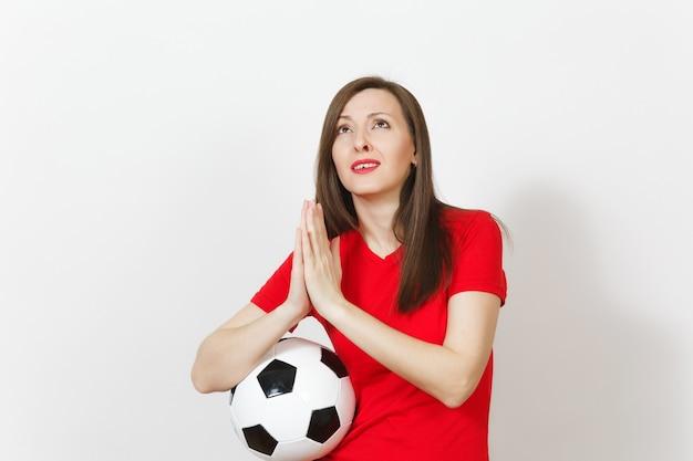 Europäischer fußballfan oder spieler der jungen frau in roter uniform gefaltete hände im gebet, fußball isoliert auf weißem hintergrund halten. sport spielen fußball-lifestyle-konzept. warten sie einen besonderen moment. wünsch dir was.