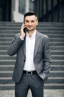 Europäischer geschäftsmann, der auf handy nahe bürogebäudehintergrund spricht