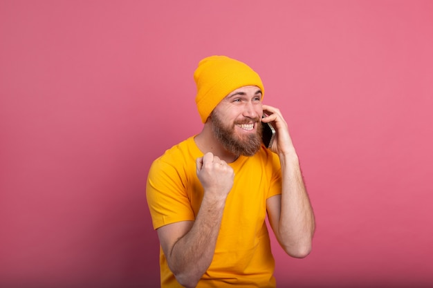 Europäischer gutaussehender mann, der auf dem smartphone spricht, das stolz schreit und sieg und erfolg feiert, sehr aufgeregt auf rosa