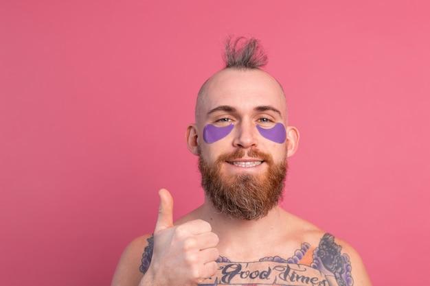 Europäischer hübscher bärtiger tätowierter oben ohne mann mit lila augenklappenmaske, die zur kamera auf rosa aufwirft