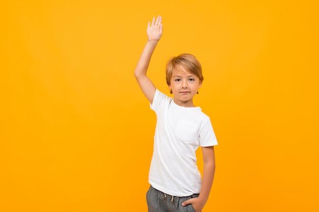 Europäischer junge in einem weißen t-shirt mit modell mit einer erhabenen hand auf einem orangefarbenen hintergrund mit kopienraum