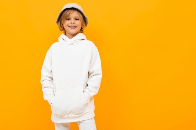 Europäischer junge mit einem panama in einem hellen kapuzenpulli auf orange