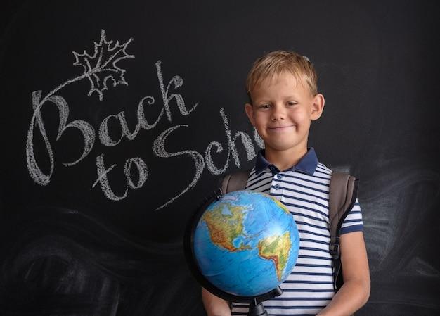 Europäischer junge mit physischem globus auf schwarzer schulbehörde mit inschrift zurück zur schule