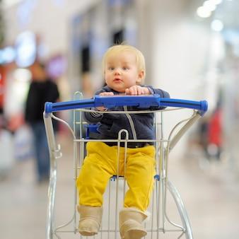 Europäischer kleinkindjunge, der im einkaufswagen sitzt