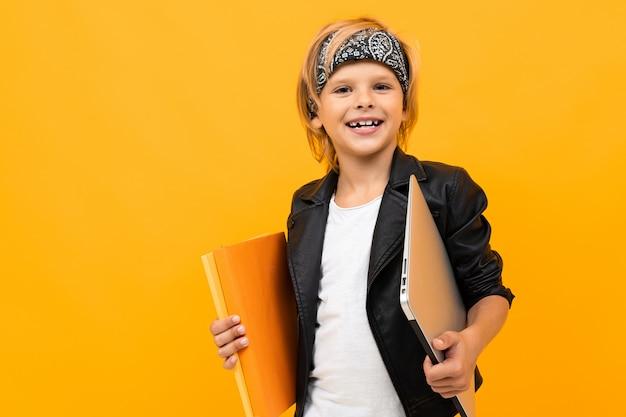 Europäischer lächelnder junge hält einen ordner mit dokumenten und einem laptop auf gelbem studio