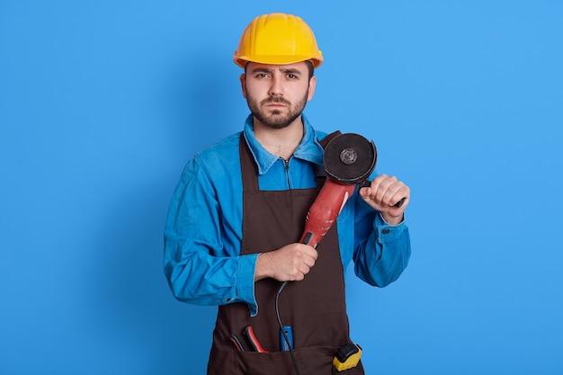Europäischer männlicher bauarbeiter mit schleifmaschine in den händen, die isoliert über blauer wand aufwirft, betrachtet kamera mit ernstem ausdruck, schutzhelm und schürze tragend, vorarbeiter, der bereit ist, zu arbeiten.