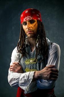 Europäischer mann im bild eines piraten auf einem dunklen hintergrund