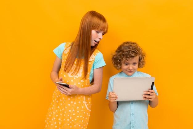 Europäischer rothaariger überraschter junge und mädchen mit dem telefon und tablette lokalisiert auf gelbem hellem hintergrund.